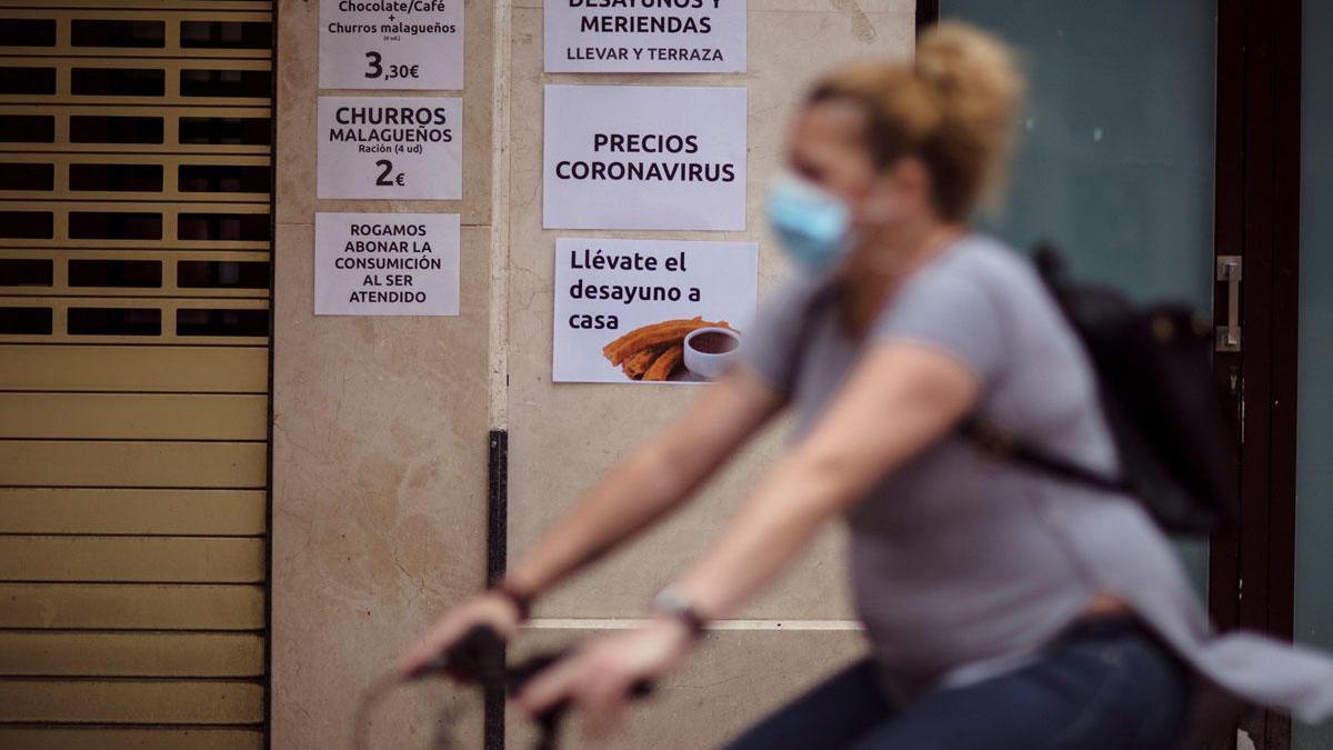 Málaga se acerca ya a los 2.500 casos activos. En la imagen, una ciclista pasa por delante de una cafetería del Centro