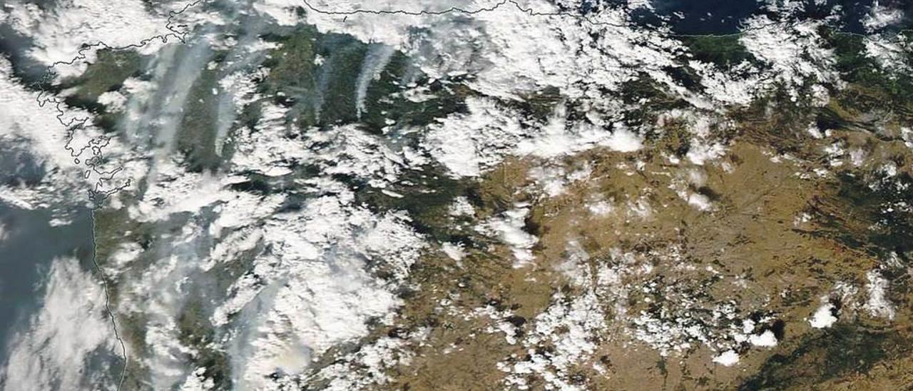 """Las columnas de humo de los incendios de Asturias, Galicia y el norte de Portugal sobresalen entre las nubes en una imagen """"Modis"""" tomada el pasado lunes."""