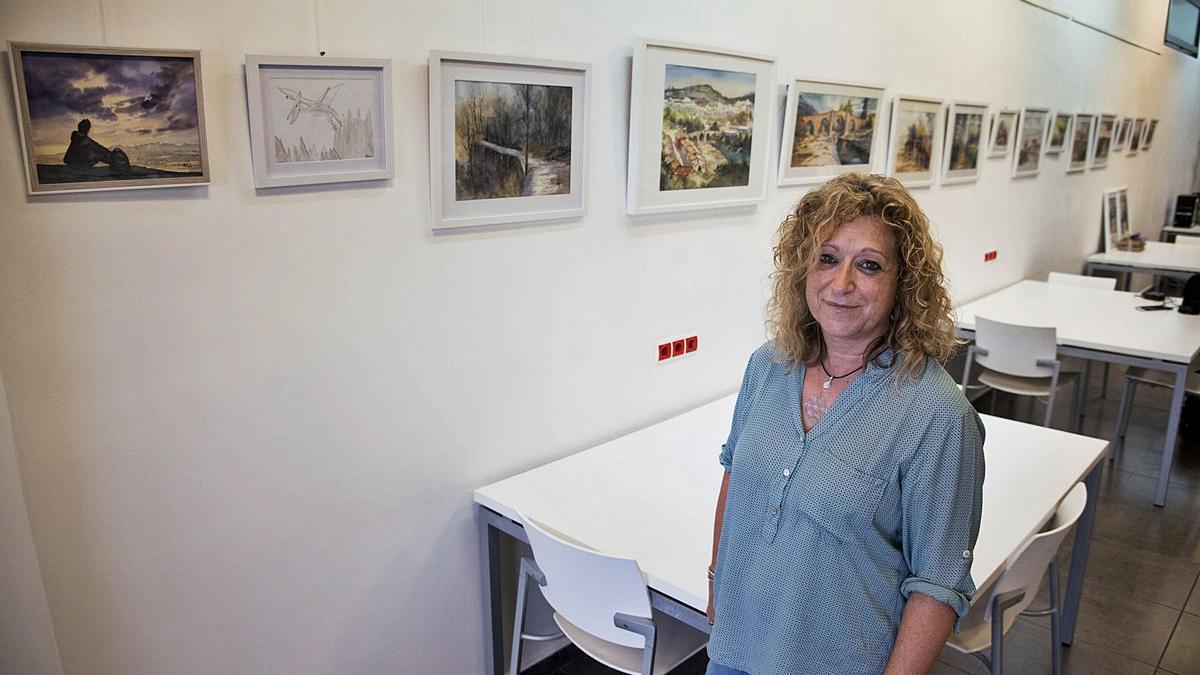 Yolanda Urango mira a càmera amb les seves aquarel·les de temàtica vilomarenca al seu darrere, a la biblioteca del Pont   MIREIA ARSO