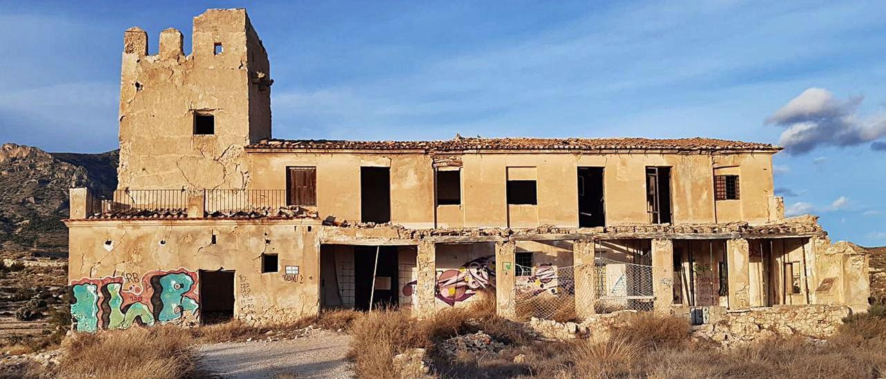La torre deteriorada tiene adosada una casa que se encuentra en ruinas. |