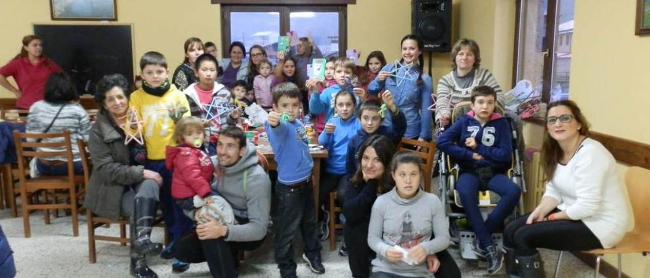 """Niños, padres y monitoras muestran los adornos navideños hechos en el taller de """"Emburria""""."""