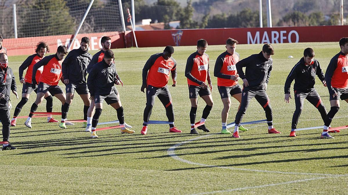 Los jugadores del Sporting realizan un ejercicio con el preparador físico, Eduardo Domínguez, a la izquierda, en el entrenamiento de ayer. | Ángel González