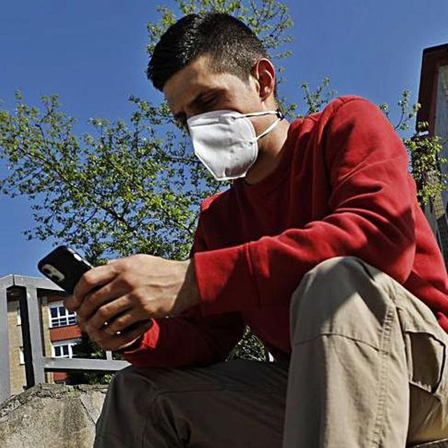 Adrián Fernández mira su teléfono móvil sentado en unas escaleras del barrio de Otero, en Oviedo.   Luisma Murias