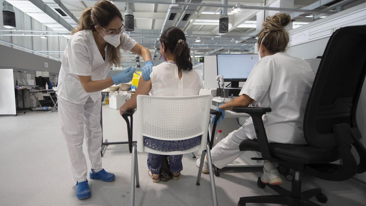 Una joven recibe la primera dosis de la vacuna Pfizer en el Hospital Zendal.