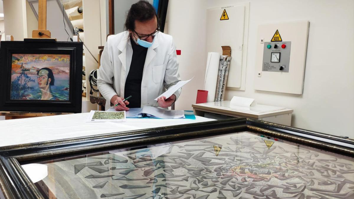 Un restaurador comprovant una de les obres de Salvador Dalí que es deixaran en préstec per una exposició a Itàlia