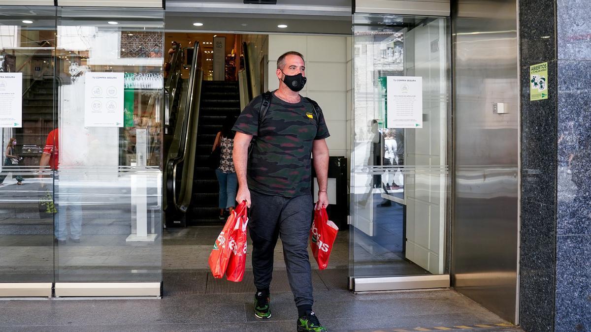Un hombre sale con varias bolsas de un centro comercial.