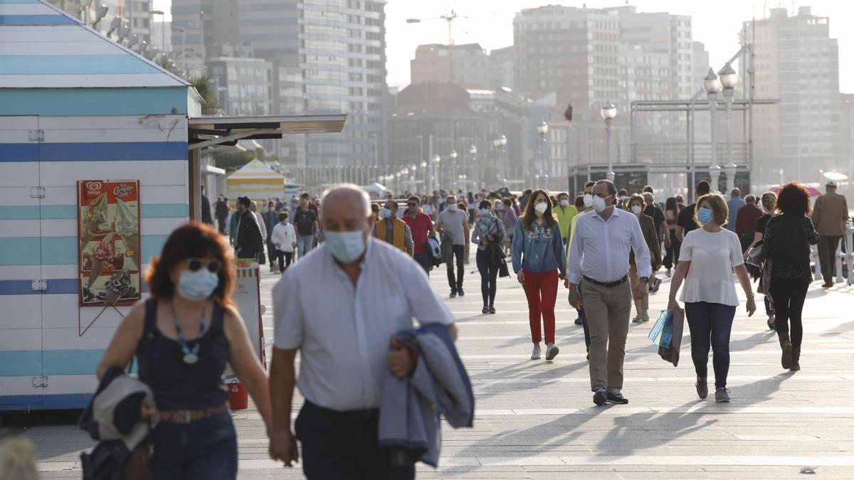 Ciudadanos en el paseo del muro de Gijón. ÁNGEL GONZÁLEZ