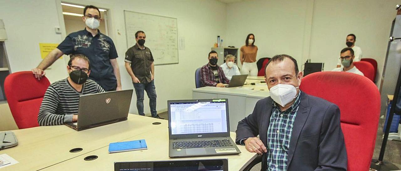 Los investigadores en el laboratorio y ante el reloj que identifica a la Politécnica de la UA. | INFORMACIÓN