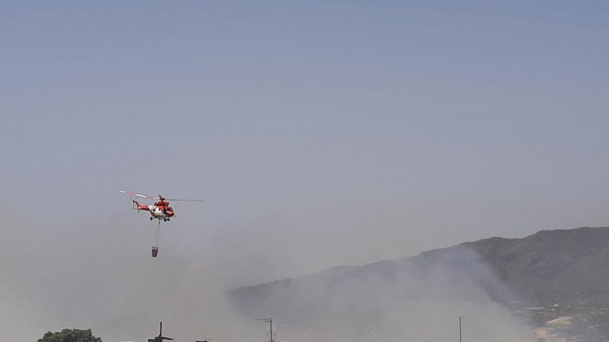 Un helicóptero descarga agua sobre las llamas declaradas en El Paso.