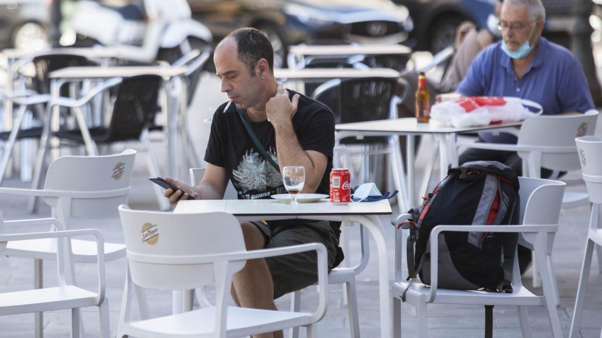 Un hombre sin mascarilla en una terraza de Valencia.