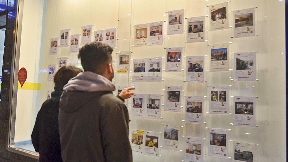 Dos jóvenes miran los anuncios de una inmobiliaria.     // ROLLER AGENCIA