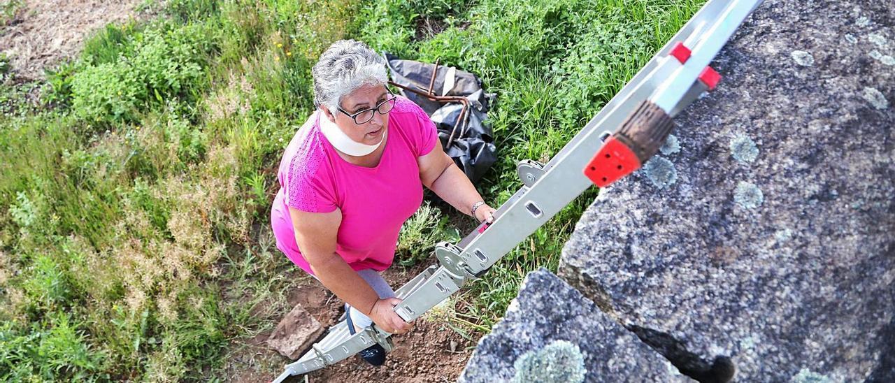 Rosa Pereira accediendo a su vivienda deFigueiró, para la que usa una escalera, ayer.