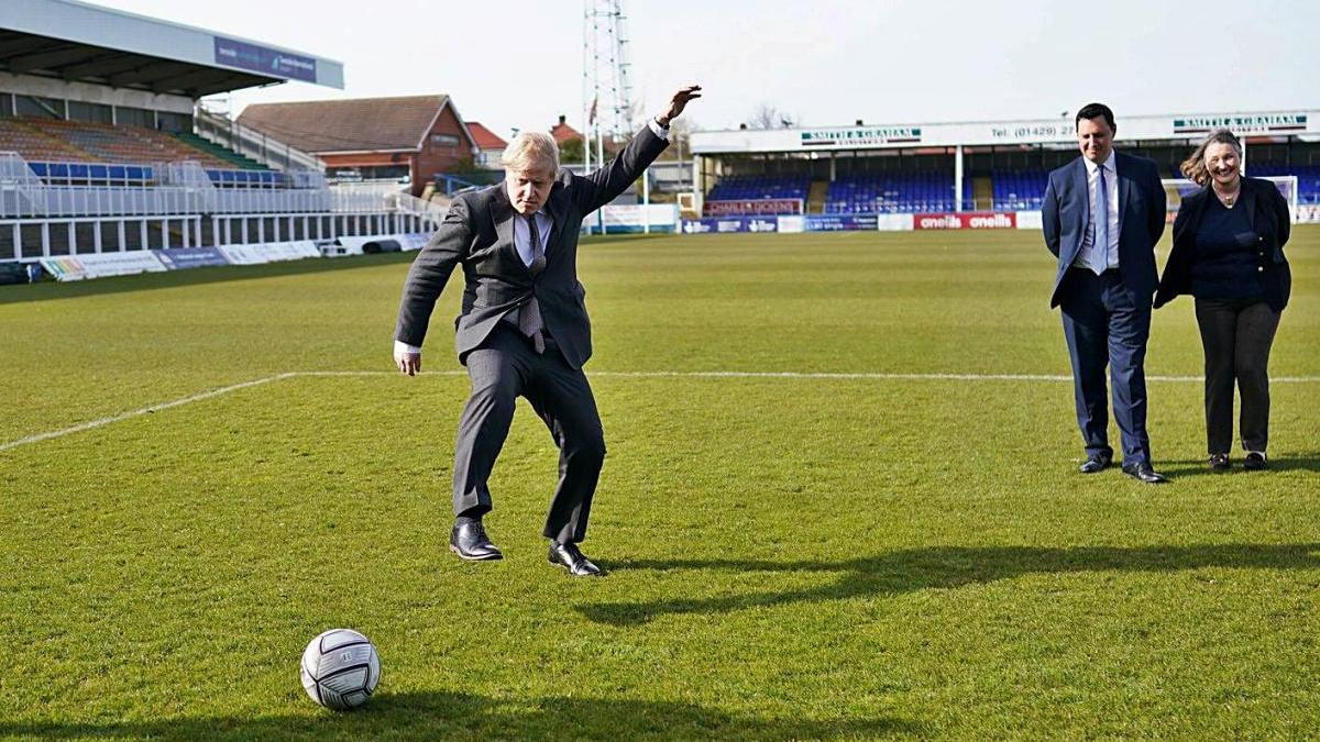 Boris Johnson xuta una pilota de futbol ahir durant una visita.
