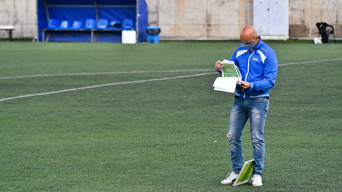 Chus Trujillo, UD Tamaraceite coach, looks at some notes on the Juan Guedes pitch last week.  |  |  JUAN CASTRO