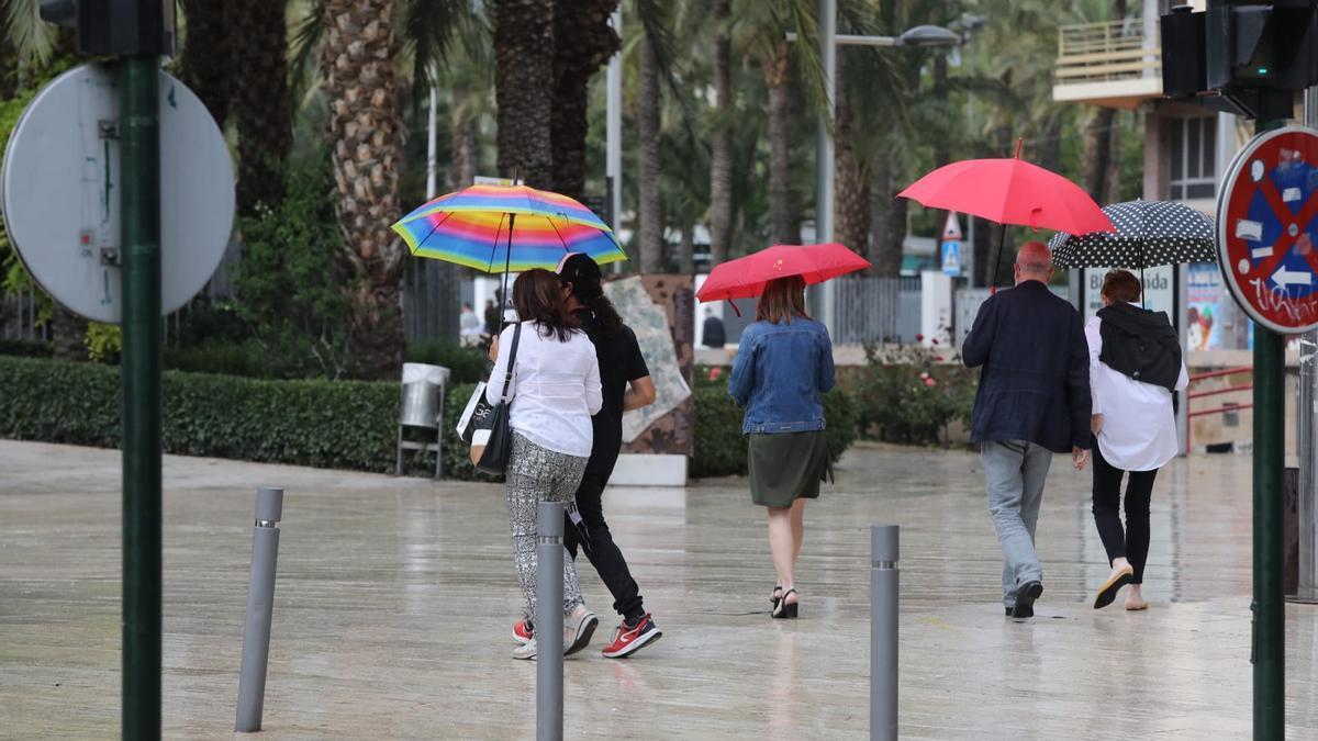 Los ilicitanos, viendo cómo estaba hoy el cielo, ha sido previsores y han salido a la calle con paraguas