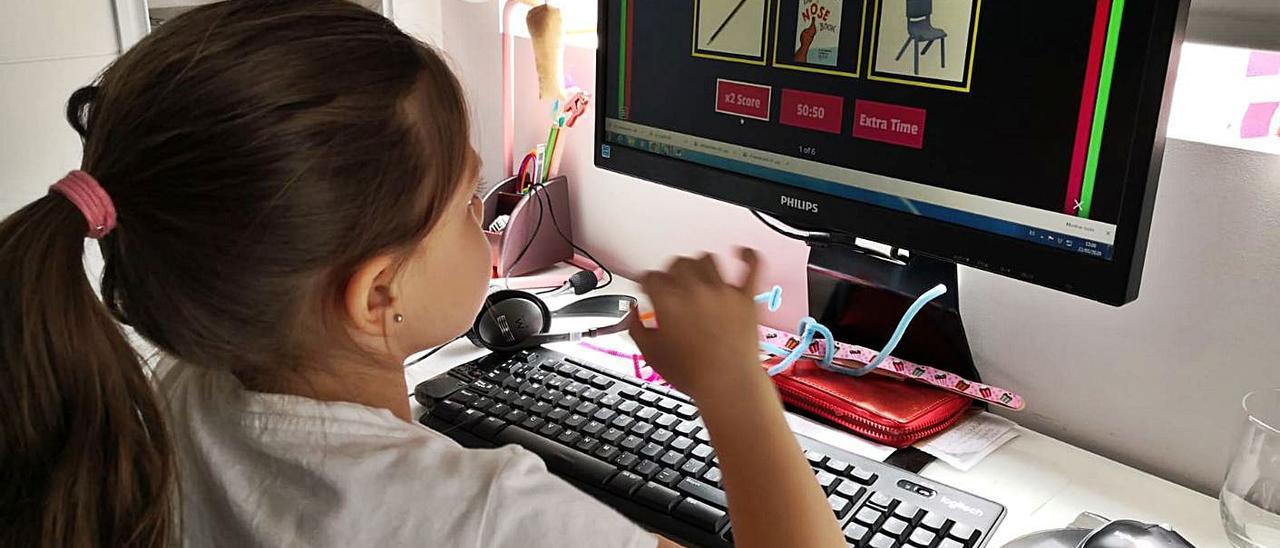 Una niña realiza tareas desde un ordenador en casa durante el confinamiento.
