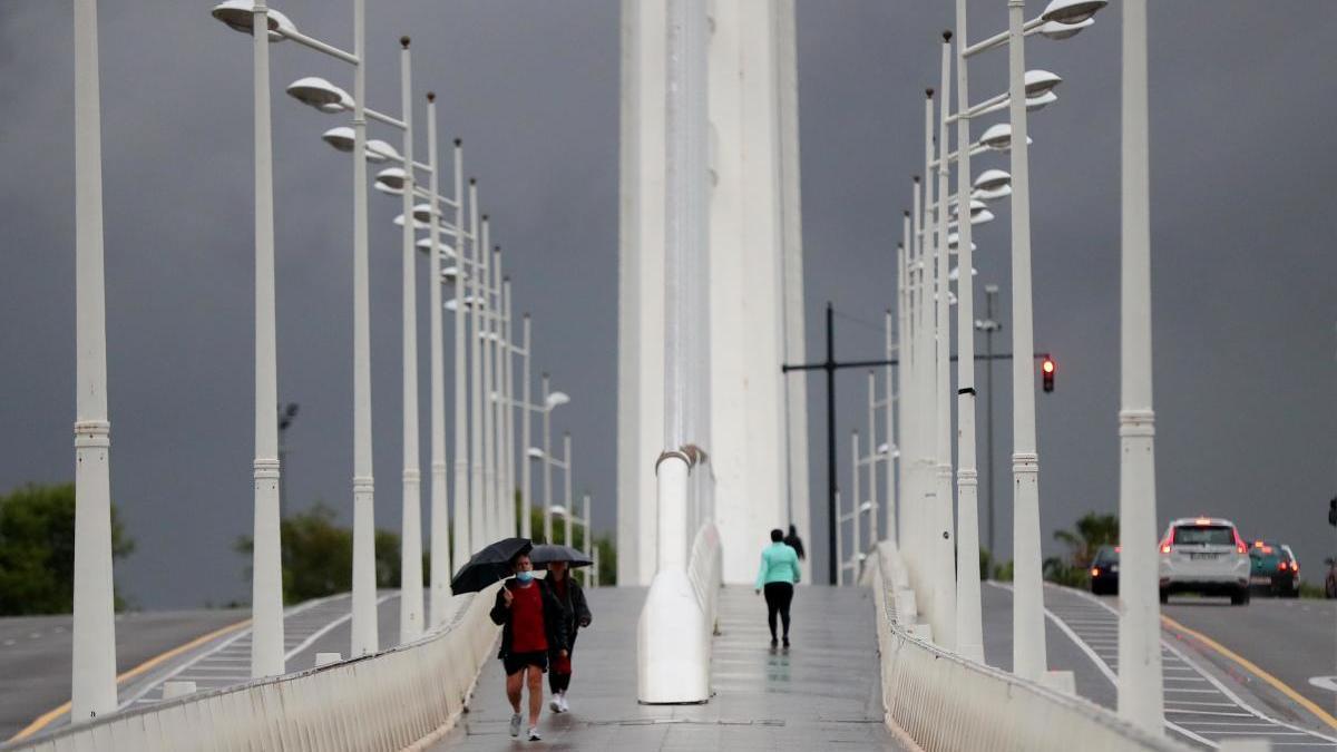 Peatones caminan sobre el puente de l'Assut de l'Or en València.