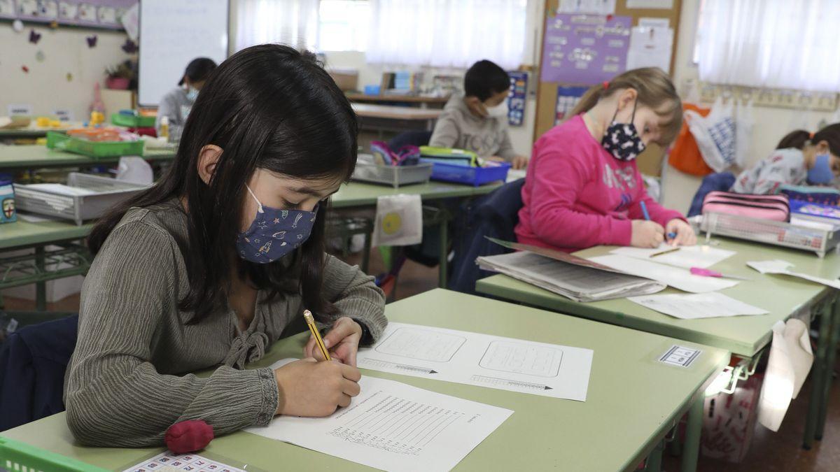Alumnos con mascarillas en un aula.