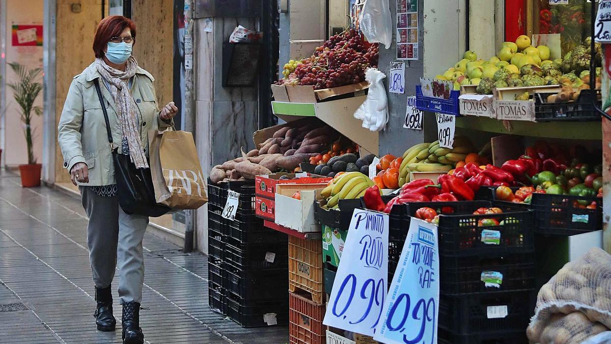 Una vecina de Torrent pasa junto a una frutería en una de las principales zonas comerciales de la ciudad. | JM LOPEZ