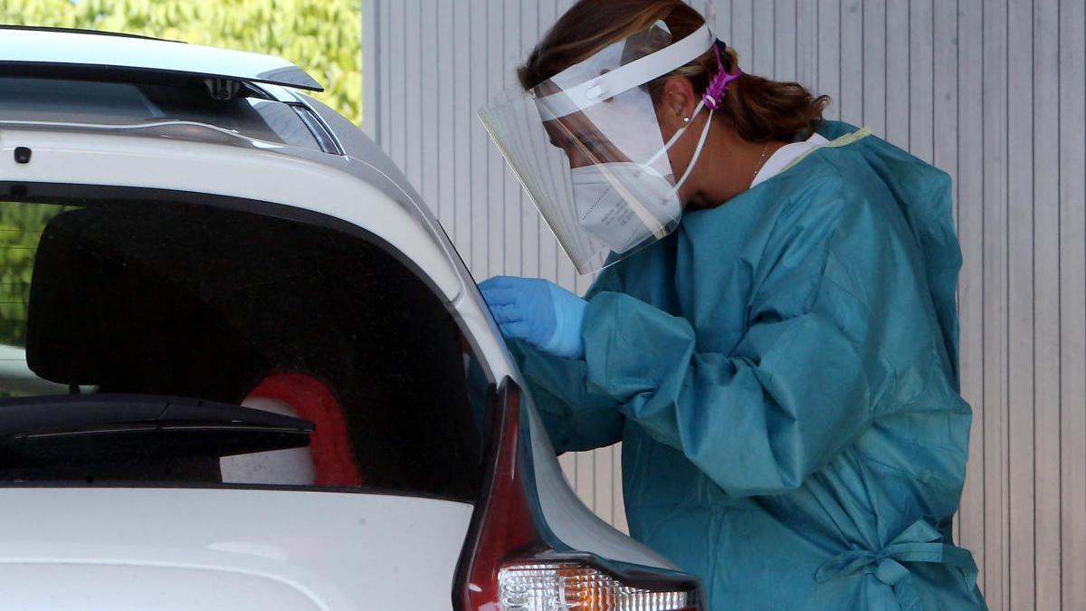 Una mujer realiza la prueba PCR a personas desde su coche en la zona habilitada del Meixoeiro. // Marta G. Brea