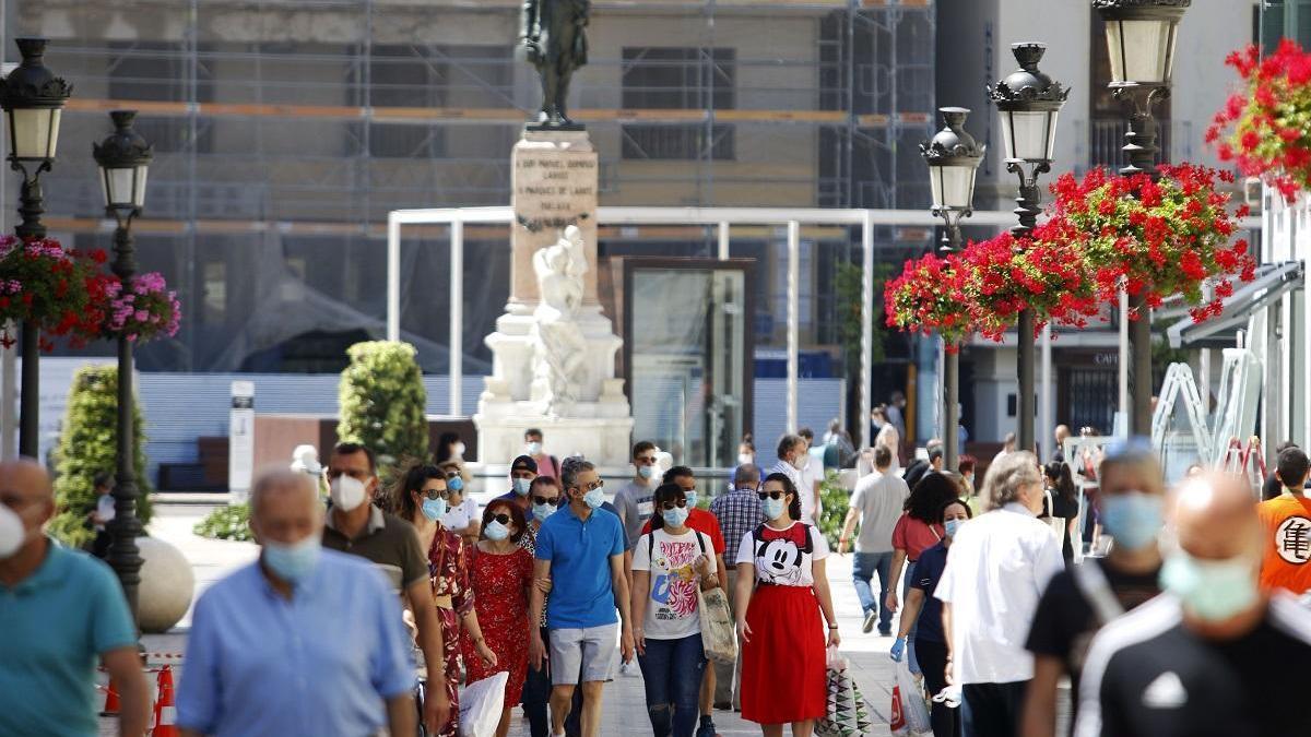 Calle Larios con transeúntes protegidos con mascarillas