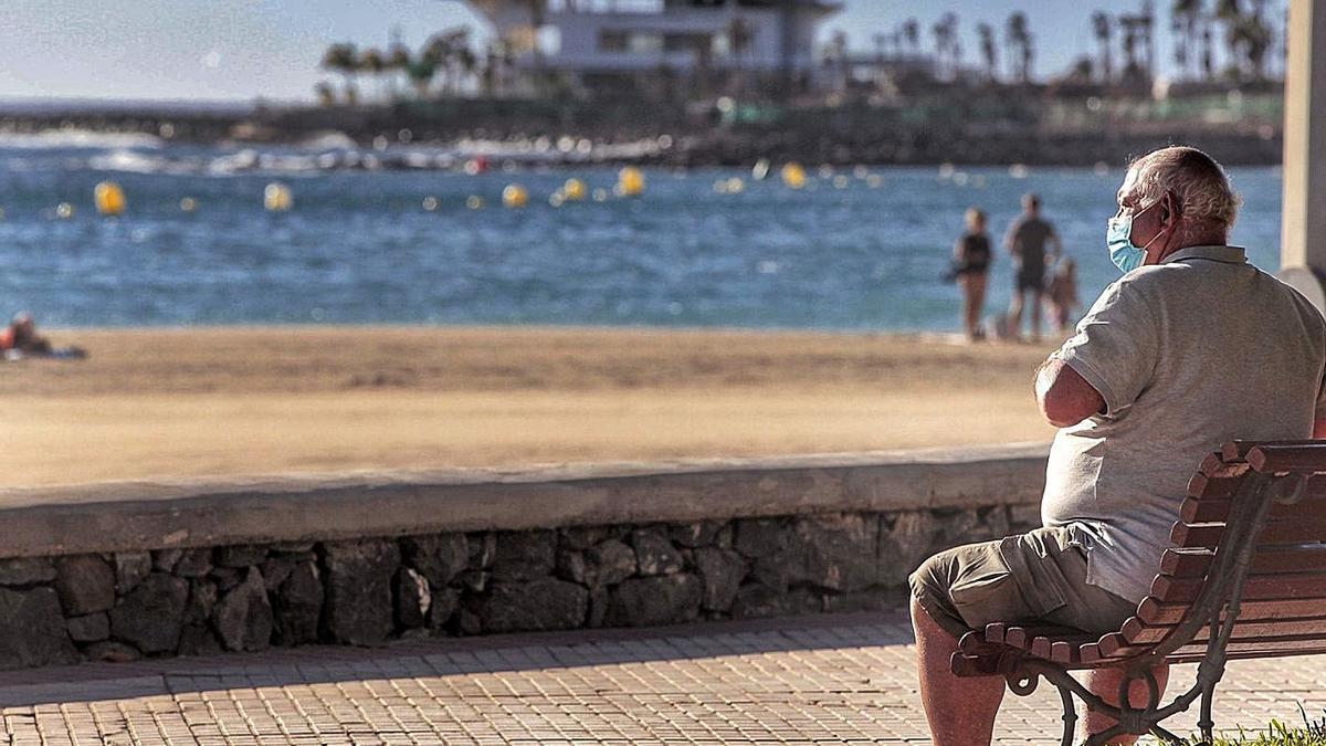 Un turista contempla la playa sentado en un banco de Los Cristianos.     MARÍA PISACA