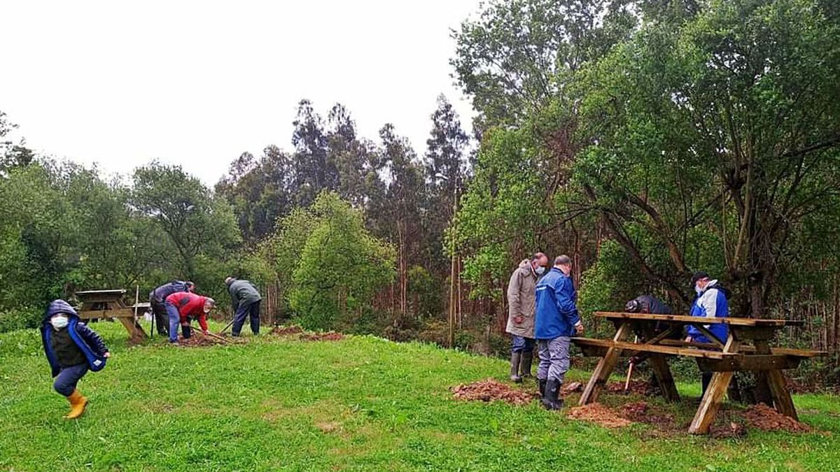 Vecinos de San Martín del Mar, el pasado domingo, adecentando el parque de la parroquia. | O. P.