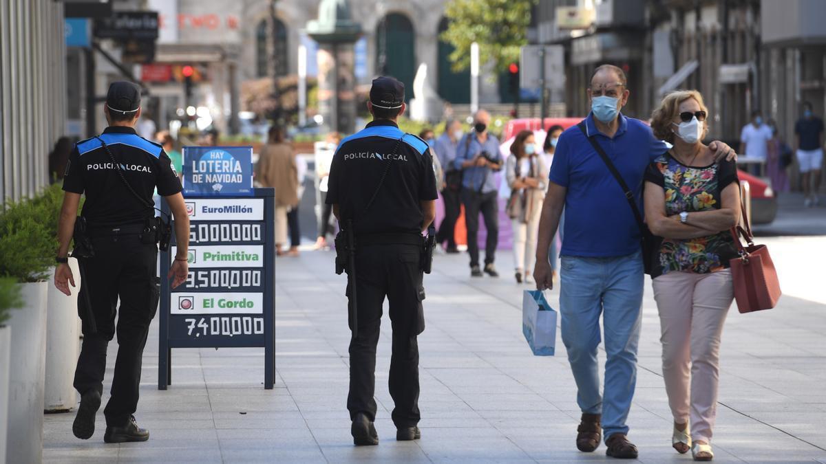 Agentes y ciudadanos con mascarilla en A Coruña en una imagen de archivo.
