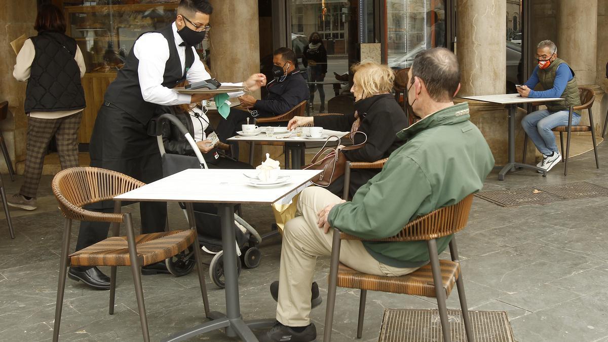 Un camarero sirve a un cliente en una terraza.