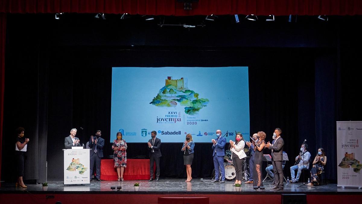 El premiado y los finalistas, arropados en el escenario por organizadores del acto.