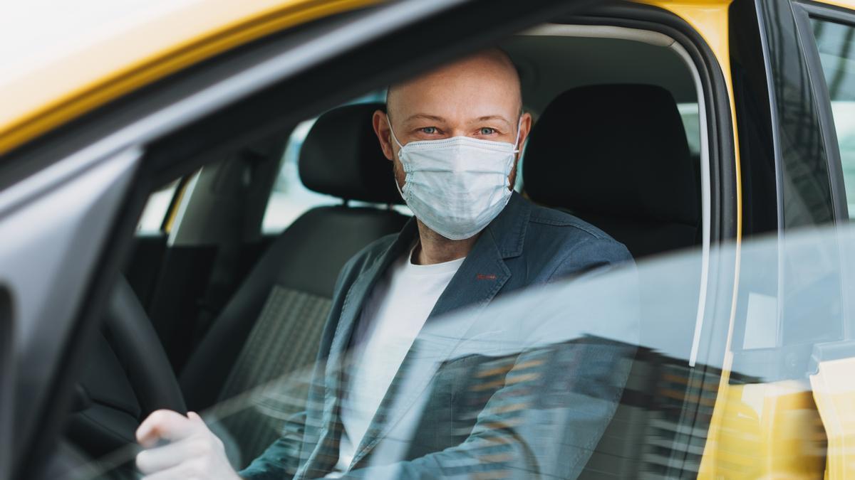 Un hombre con mascarilla en su vehículo