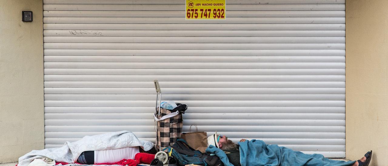 Dos personas durmiendo en pleno día en la entrada de un comercio que recientemente ha cesado su negocio: una zapatería, en la Rambla, cerca del Portal de Elche.