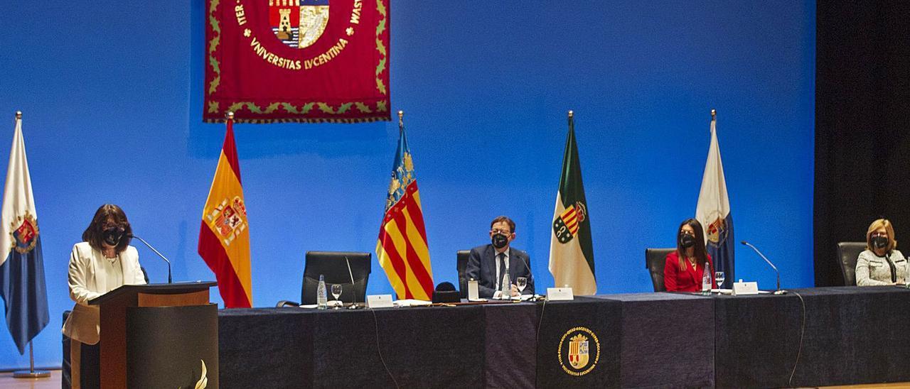 La rectora pronuncia su discurso ante la atenta mirada del presidente Puig, la consellera de Universidades y la secretaria de la UA, Ester Algarra, en la mesa presidencial.