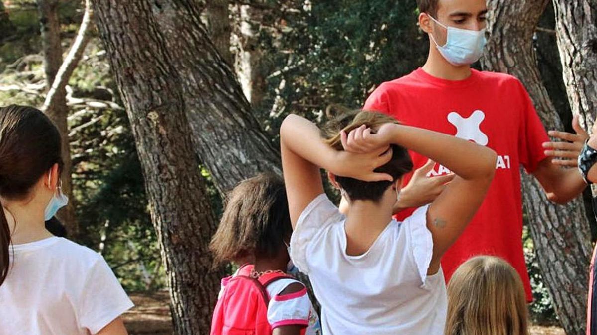 Un monitor de lleure i un grup de nens i nenes es diverteixen jugant | ACN
