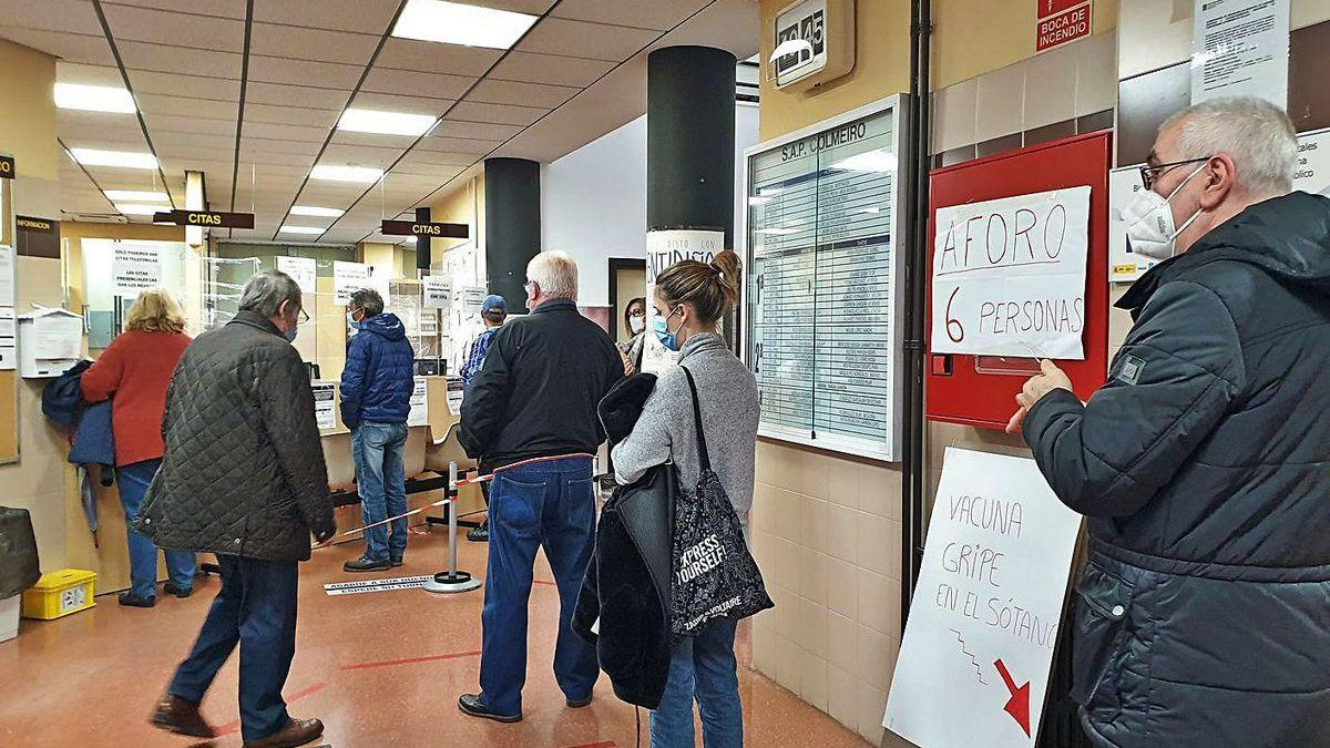 Pacientes hacen cola en un centro de salud para ponerse la vacuna de la gripe.