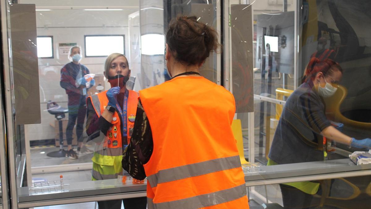 Una empleada se practica la PCR bajo la supervisión de una sanitaria en el centro logístico de Amazon.