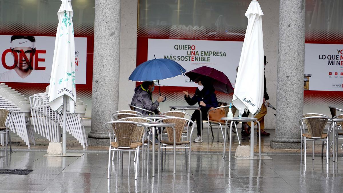 Una pareja se protege de la lluvia en una terraza de la Plaza Mayor.