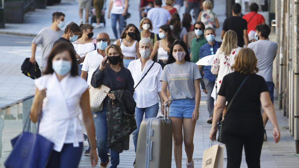 Personas con mascarilla caminando por el centro de Vigo. // Alba Villar