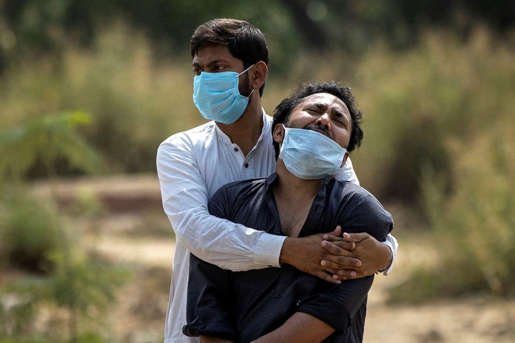 Dos hombre lamentan la pérdida de un ser querido por coronavirus en India, donde la pandemia no da tregua