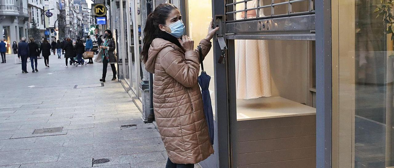 Una mujer cierra un comercio  en la calle Príncipe en Vigo.