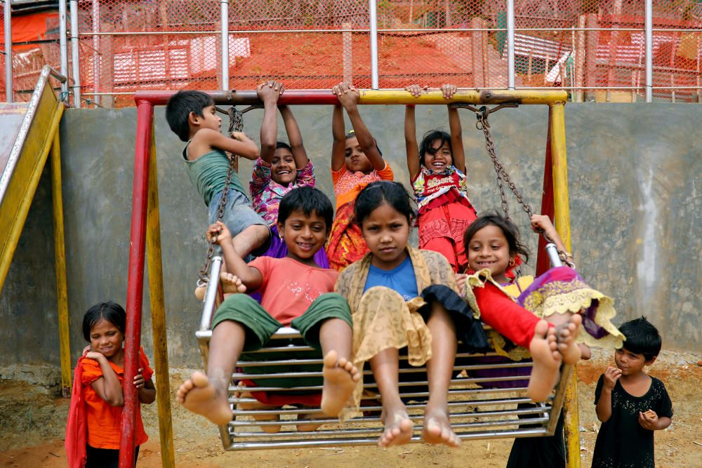 Rohingya refugee children play on a swing at a ...