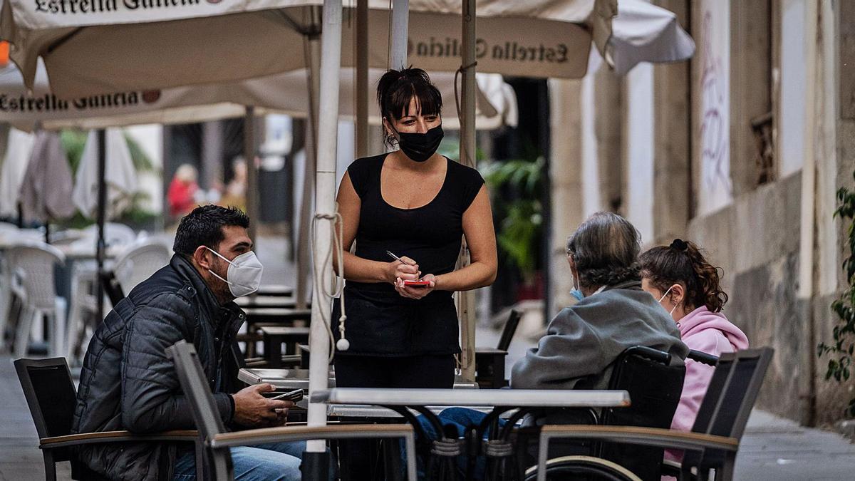 Una camarera atiende a tres clientes en una terraza de Santa Cruz de Tenerife.     ANDRÉS GUTIÉRREZ