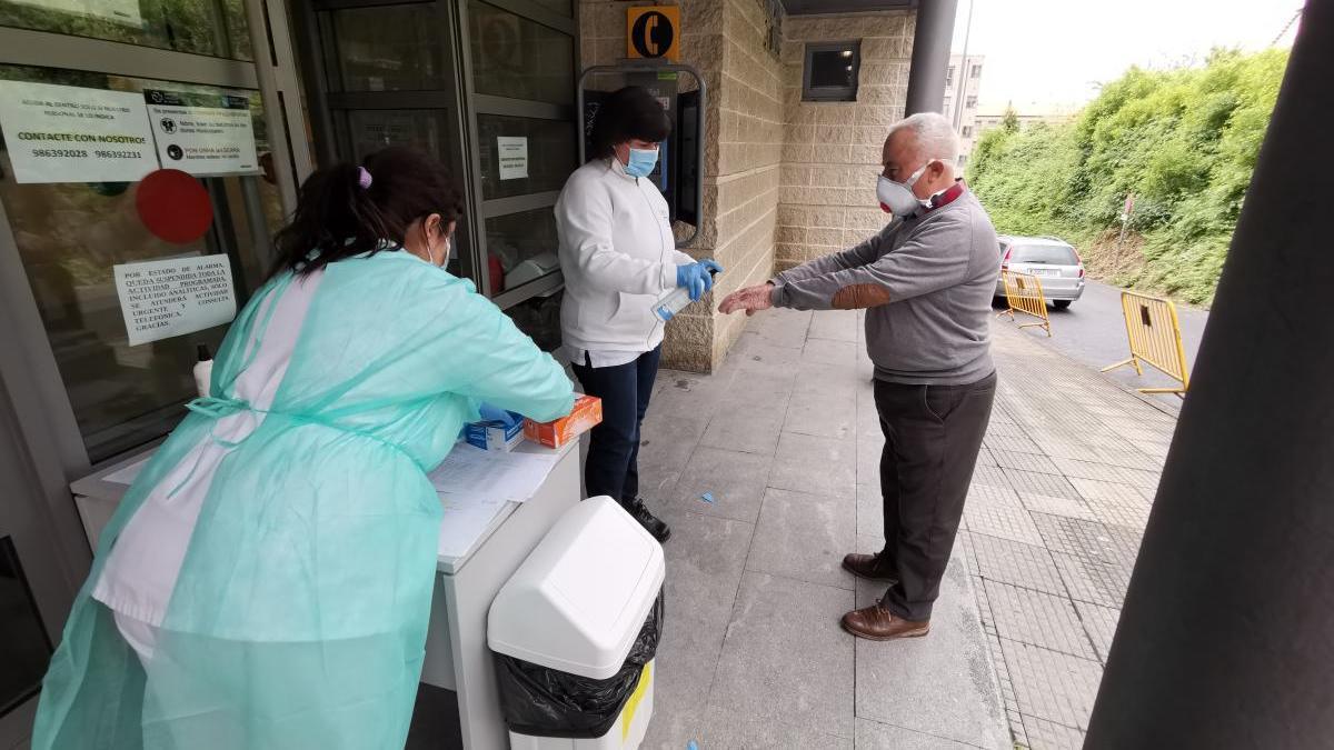 Dos sanitarios y un paciente toman las medidas de seguridad recomendadas antes de entrar en el Centro de Salud de Cangas. // Santos Álvarez