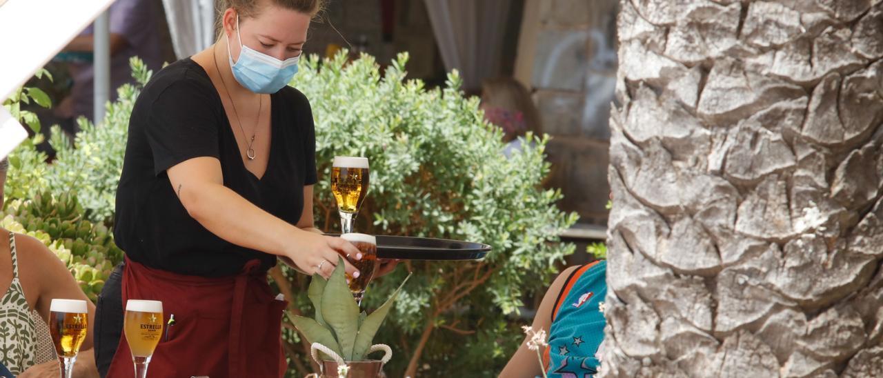 Una camarera sirve unas cañas en una terraza