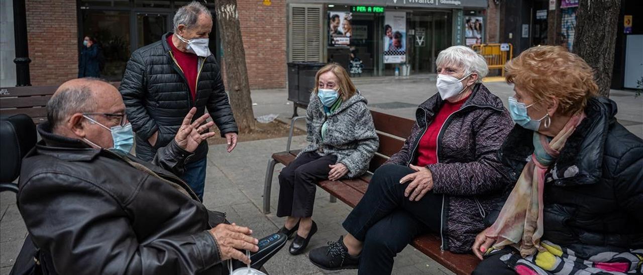 Un grupo de jubilados conversan en la calle.
