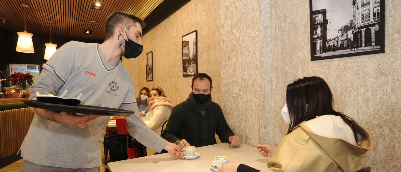 Un camarero sirve un café a los clientes de un bar en A Estrada. // Bernabé / Javier Lalín