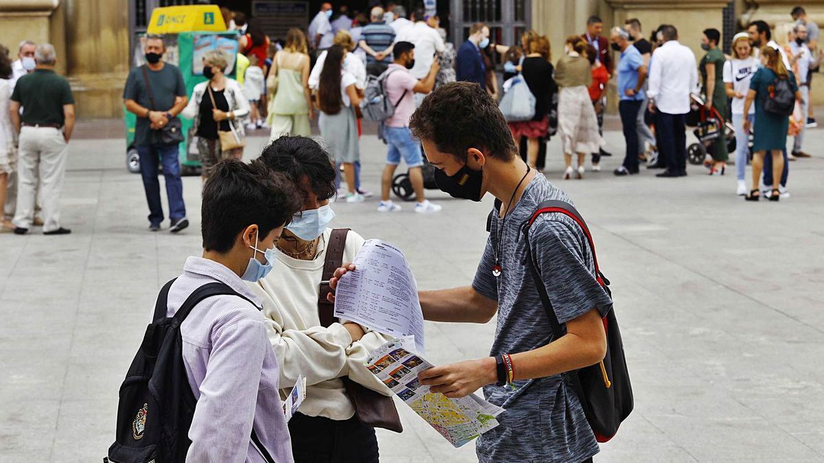 Una familia de turistas revisa unos planos este  sábado en la plaza del Pilar, el lugar más visitado.    JAIME GALINDO