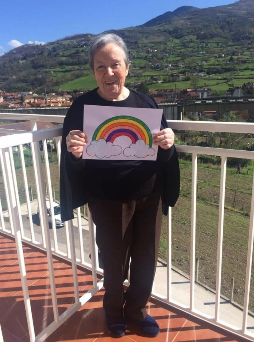 Raquel Fueyo muestra un dibujo de un arcoíris.