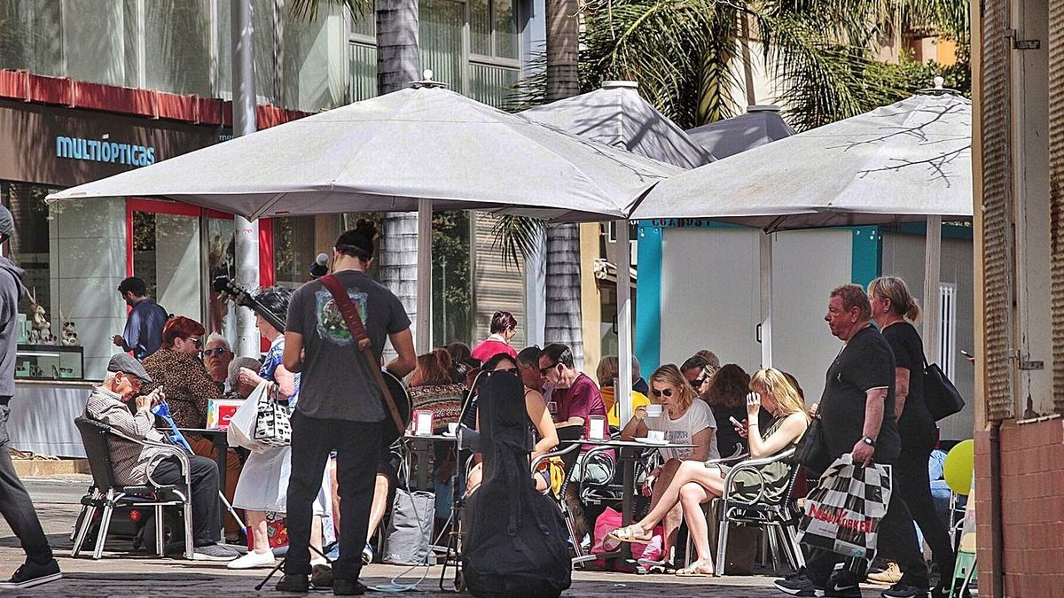 Un músico actúa para los ocupantes de una terraza de Santa Cruz de Tenerife.     MARÍA PISACA