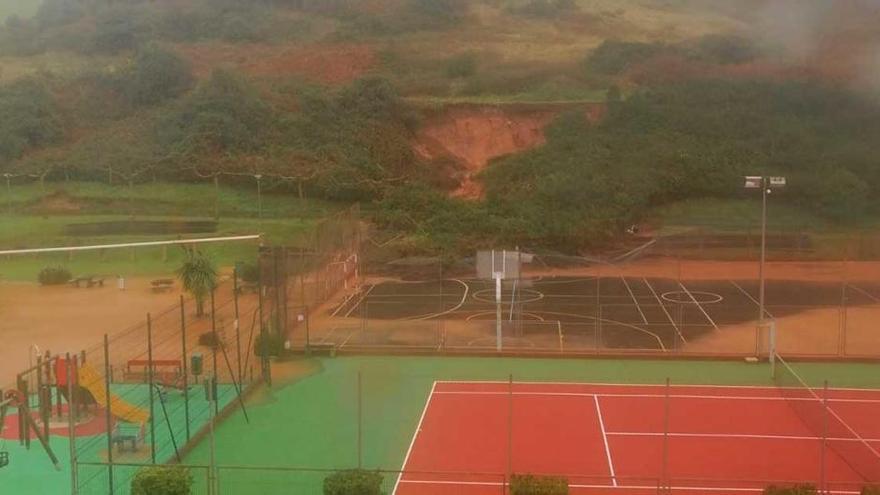 Un argayo sepulta parte del recinto deportivo de la urbanización de Xivares